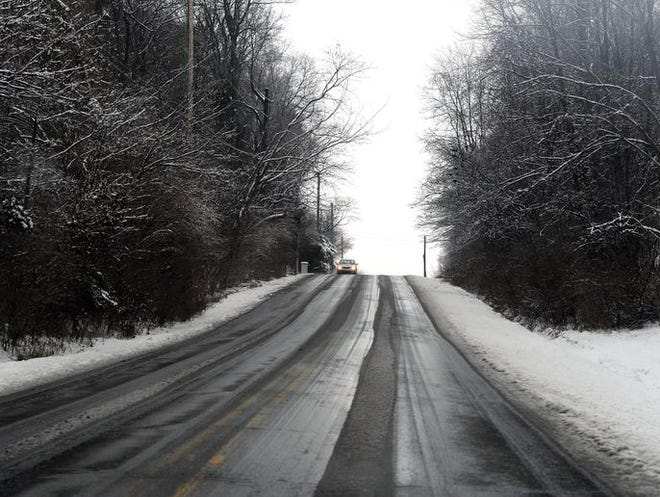 A car makes its way down Lee Road in Lawrence as snow fell Dec. 14, 2013, near the Fort Harrison State Park's dog park.