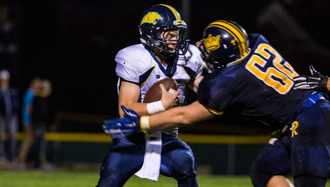 Iowa City Regina's Jared Brinkman (62) goes to tackle Cascade's Derek Lierance (2) during play in Iowa City on Friday, September 5, 2014. (Justin Torner/Freelance for the Press-Citizen)