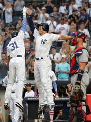 New York Yankees' Aaron Hicks, left, celebrates with Giancarlo Stanton near Atlanta Braves catcher Tyler Flowers after Hicks hit a two-run home run during the first inning of a baseball game Tuesday, July 3, 2018, in New York. (AP Photo/Frank Franklin II)