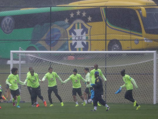 Member of the Brazilian national soccer team exercise in the rain during a team training session in Teresopolis, Brazil, Thursday, June 19, 2014. Brazil plays in group A of the 2014 soccer World Cup. (AP Photo/Andre Penner)