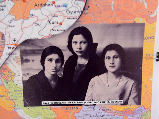 A close-up of a photograph of Asya Titova with her sister and a friend in Moscow. The photo is part of a posterboard collage detailing Titova's life.