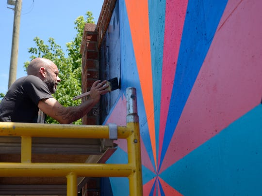 Artist Gabriel Shaffer works on a mural on South Lexington Avenue in downtown Asheville in 2013. The mural spans 70 feet and consists of traditional barn quilt patterns using bright modern colors.