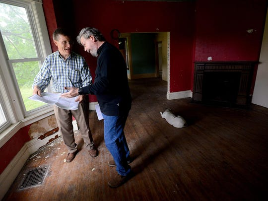 Ingham County Treasurer Eric Schertzing, left, talks with Curt Sonnenberg, a member of the Lansing city historic district commission on Thursday while showing him a map of the properties that will be available at auction on July 23. The two were at an open house for a 130-year-old property on Cherry Street, in the historic Cherry Hill neighborhood.