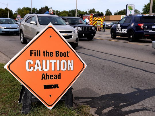 """A double-sided sign on the side of the road warns drivers that firefighters are out collecting donations for the """"Fill the Boot"""" campaign, while traffic is backed up on Cedar Street Wednesday as police investigate the scene where a firefighter was hit by a vehicle."""