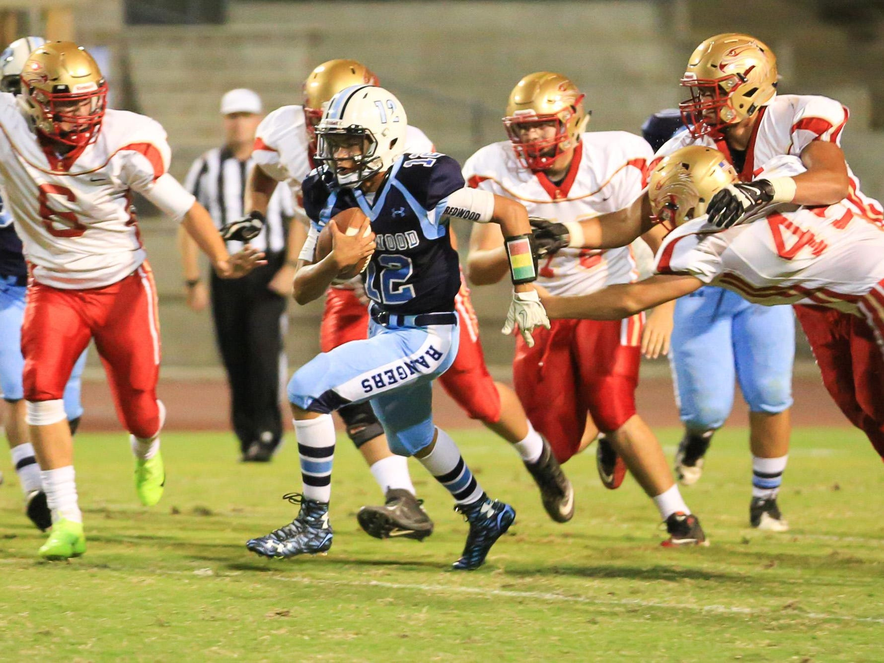 Redwood's QB Frankie Ayon (12) rushes downfield against Centennial in a non-league game.