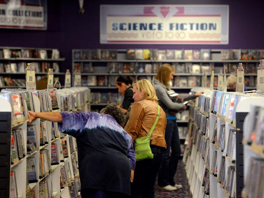 Customers look through the different titles for sale at Video To Go on Sept. 29, 2015. Video To Go, in Frandor, is closing after more than 30 years in business.