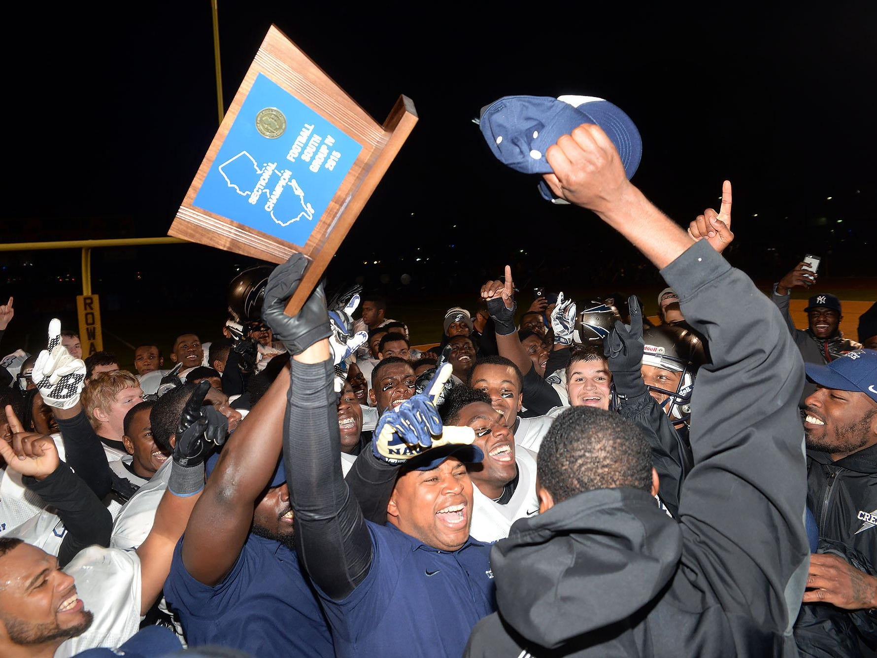 Timber Creek coach Rob Hinson (holding trophy) celebrates with his Chargers after their 28-24 win over Shawnee in the South Jersey Group 4 final on Sunday at Rowan.