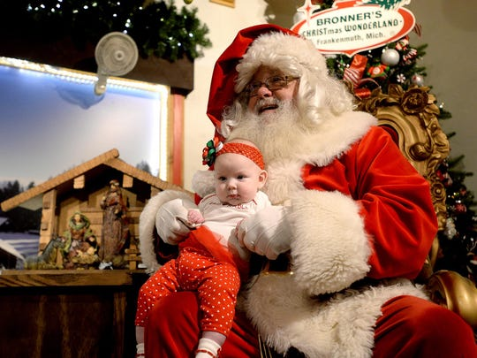 Five-month-old Layla stays calm while sitting on Santa's lap as her parents George Ludington and Ashley Newton, not pictured, snap photographs at Bronner's Christmas Wonderland in Frakenmuth.