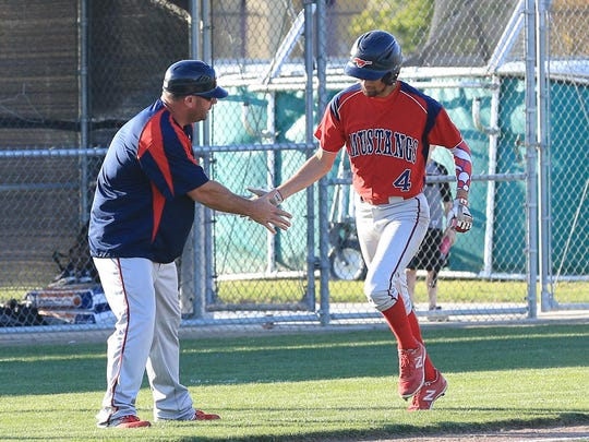 Jesse Macias, right, celebrates with Mustangs' coach