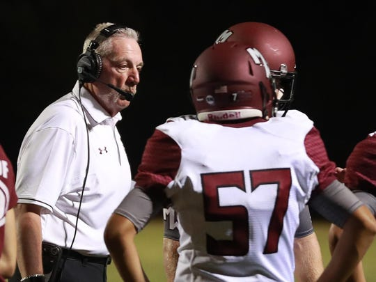 Mt. Whitney football coach Marty Martin speaks with a player during a game.