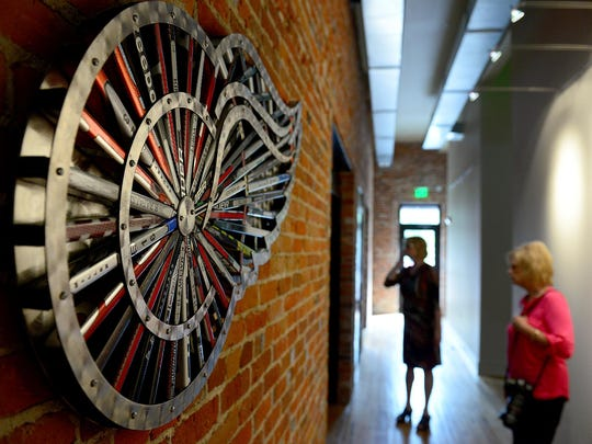 People walk down a hallway in the new headquarters of Oracle Financial Solutions Tuesday, September 29, 2015, next to a piece of artwork that's the Detroit Red Wings logo made out of hockey sticks. Oracle has moved it's headquarters to the first floor of two newly renovated 19th Century buildings in Mason.