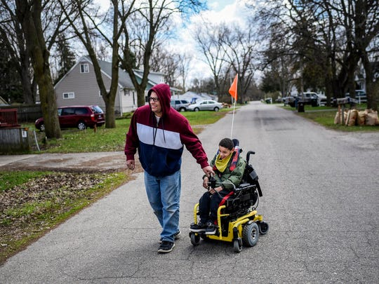 Brian Hagler, left, and his son Chris, 8, get some fresh air on the street outside their home during Brian's break from work on April 21, in Lansing. Chris used speech, physical and occupational therapies provided by his school before the coronavirus outbreak restrictions. Brian can't use online resources for his son's learning because Chris is visually impaired. (Nick King/Lansing State Journal via AP)