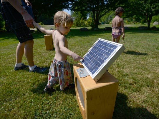 Next generation? A visitor examines a solar panel in Grand Isle State Park.