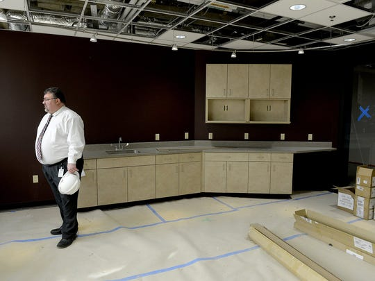 Doug Church, a facilities manager with the State of Michigan, looks out toward the downtown Lansing skyline from the windows of a new kitchen area on a renovated floor in the Mason Building on March 6, 2015.