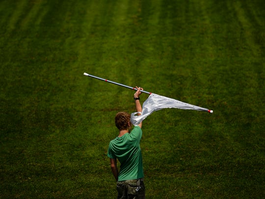 Dominic Gerbec twirls a flag during marching band practice at Green Bay East High School on Thursday. The band is preparing to play in the National Independence Day Parade on July 4th in Washington D.C.