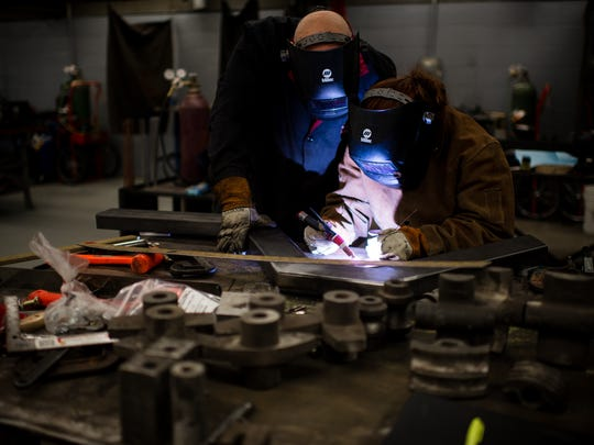 Algoma Wolf Tech teacher Russ Nockerts (left) helps junior Savannah Brunette on her welding project at Algoma High School in February 2014. High schools increasingly are adding manufacturing related programs to meet industry and student needs.