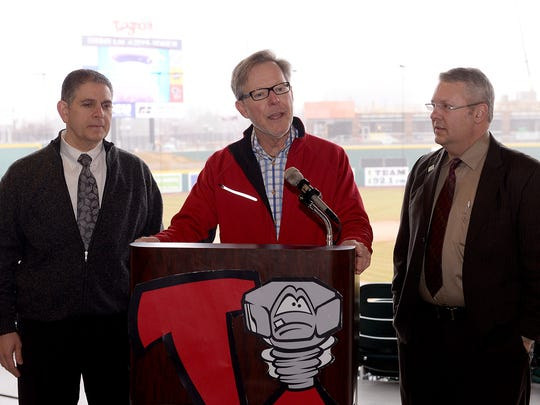 Tom Dickson, owner of the Lansing Lugnuts, center, with Lansing Mayor Virg Bernero, left, and Bob Trezise, president and CEO of LEAP, speak before ceremoniously cut the ribbon for the renovations at the Cooley Law School Stadium Thursday, April 8, 2015.