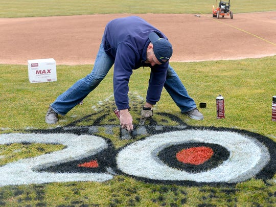 Craig Oberry, with Pioneer Athletics, paints the Lugnuts 20th anniversary logo behind home plate Thursday, April 8, 2015, at Cooley Law School Stadium.