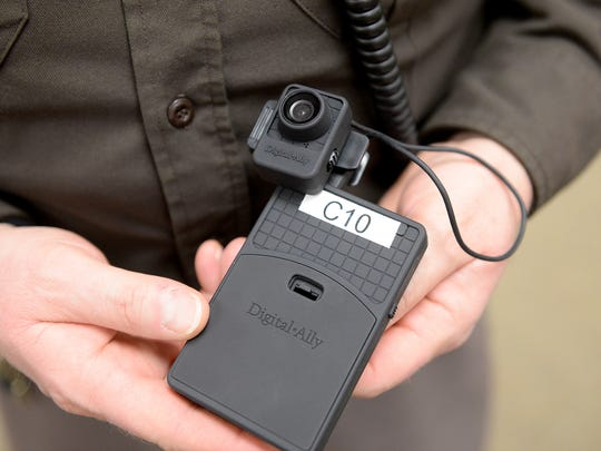 Sgt. Tom Campbell of the Eaton County Sheriff's Office, holds his body camera and the hard drive to which it records.