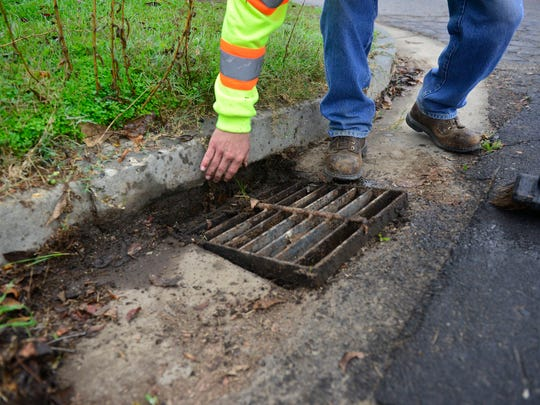 Visalia city worker Jeff Riley clears a drain in preparation for a large storm that could hit the Valley as early as tonight.