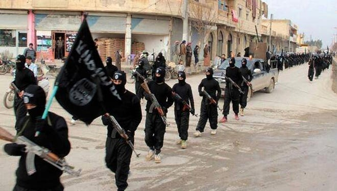ISIL fighters marching in Raqqa, Syria, in 2012.