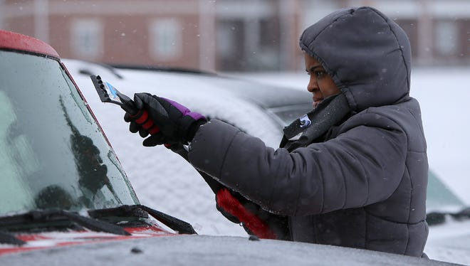 Orien Mitchell, a senior at Union University, works on scraping her windshiled clear on the campus of Uinon in Jackson on Friday.