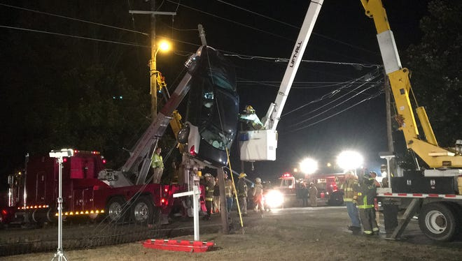 A woman was rescued from her car during the early morning of Saturday, March 26, 2016, after officials said she drove the car up a guy-wire on a utility pole in Medina, Tenn.