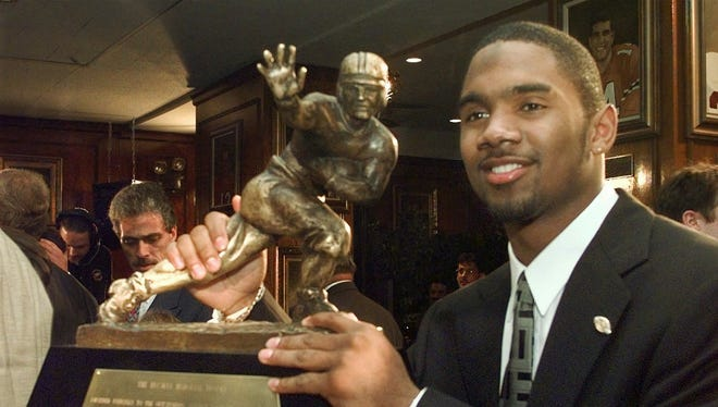 In this Dec. 13, 1997, file photo, Michigan's Charles Woodson poses with the Heisman Trophy after becoming the first primarily defensive player ever to take the honor at the Downtown Athletic Club  in New York.