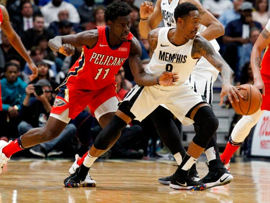 Memphis Grizzlies guard MarShon Brooks (8) keeps the ball from New Orleans Pelicans guard Jrue Holiday (11) during the second half of an NBA basketball game in New Orleans, Wednesday, April 4, 2018. The Pelicans won 123-95. (AP Photo/Scott Threlkeld)