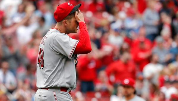 Cincinnati Reds relief pitcher Jared Hughes rubs his forehead after giving up a solo home run to St. Louis Cardinals' Yadier Molina during the seventh inning of a baseball game Saturday, April 21, 2018, in St. Louis.