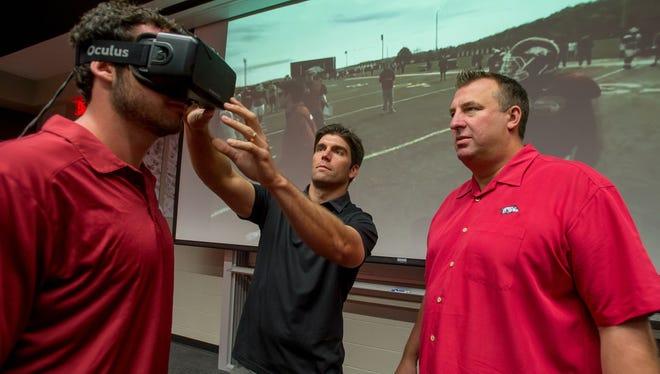 STriVR CEO Derek Belch (center) outfits Arkansas quarterback Brandon Allen (left) as Razorbacks coach Bret Bielema looks on.
