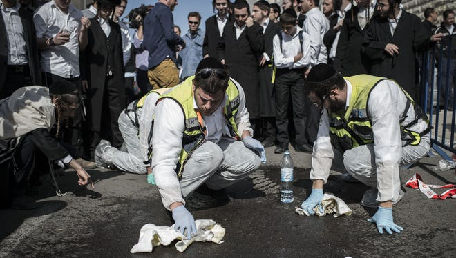 Israeli emergency personnel clean the site outside a synagogue in Jerusalem where five people were killed on Nov. 18.