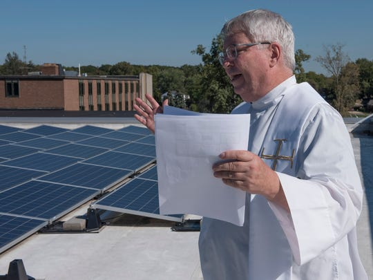 Up on the roof of the Franciscan Center, Father Charles Morris opens with a prayer.