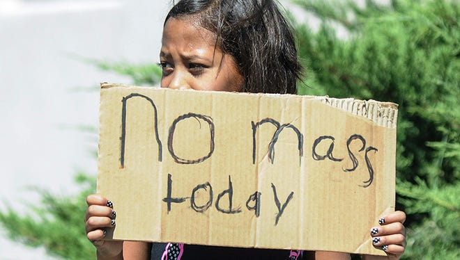 Aaliyah Doninguez, 11, stands on N. Alameda Boulevard on Sunday, Aug. 2, 2015, in Las Cruces, N.M., advising parishioners that Holy Cross Catholic Church mass is canceled. Churchgoers were left shaken during Sunday morning services after authorities say explosions occurred less than 30 minutes apart outside two Las Cruces churches.