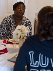 Case worker Karen Kirton talks with one of the clients at Dottie's House.
