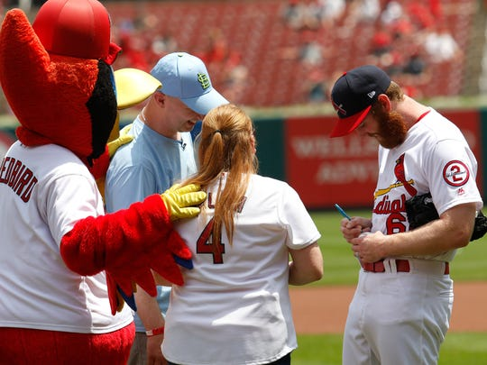 Cardinals pitcher John Brebbia signs baseballs after the first pitch as kidney transplant recipient Beth Larsen and donor Scott Hopfinger look on at Busch Stadium in St. Louis on July 1, 2018. Michael Gulledge/For the News-Leader