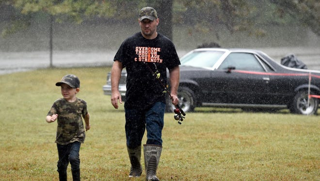 Riley Harper, 5, jogs through the rain while taking a break from fishing with his father Cory Harper of Henderson during Jakes Day in Henderson County Saturday.  The event is designed to engage kids with the outdoors.