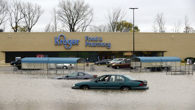 Vehicles sit stranded in the parking lot in front of the Kroger grocery store on Memorial Drive Monday, Nov. 6, 2017, in Lancaster. More than three inches of rain in 12 hours raised the level of the Hocking River high enough to prevent the lot from draining.