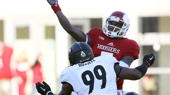 Indiana Hoosiers quarterback Tre Roberson (5) passes the ball over Purdue Boilermakers defensive end Ryan Russell (99) during the first quarter at Memorial Stadium.