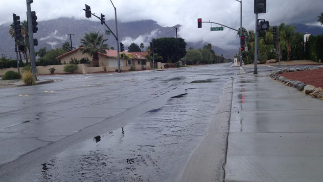 Water flows along Via Escuela in Palm Springs as a storm drops rain on the Coachella Valley on Friday, Dec. 12, 2014.