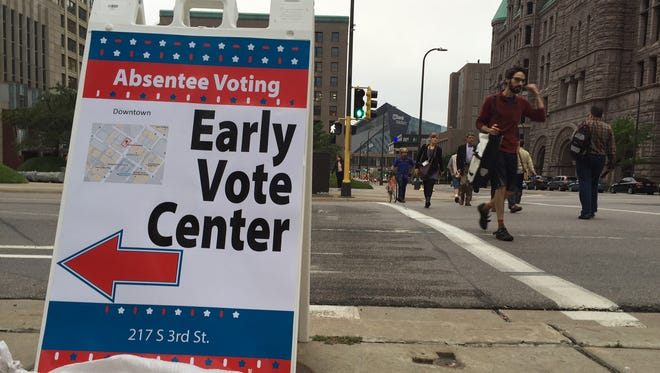 Pedestrians walk past a voting sign Sept. 23 in downtown Minneapolis. Election Day is more than a month away but the voting is already underway as Minnesota kicked off its first presidential cycle where all voters across the state can cast their ballots early.