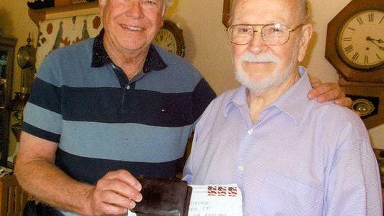 Scott Dodge pictured here with Jim Westlake and the wallet Dodge was able to return to Westlake after nearly 55 years.