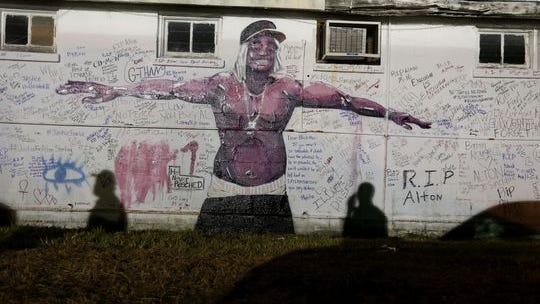 Shadows fall on a newly painted mural of Alton Sterling next to the Triple S convenience store in Baton Rouge, La., July 6, 2016. Sterling, 37, was shot and killed outside the store by Baton Rouge police. ,