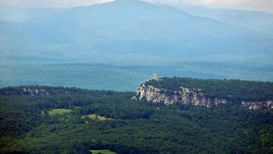 The Smiley Memorial Tower located above the Mohonk Mountain House in New Paltz is framed by the Catskill Mountains in the background. The Shawangunk Wine Trail offers views like this and more.