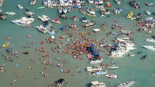 Anyone who attended a Fourth of July party at Torch Lake Sandbar over the holiday weekend is being asked to monitor themselves for symptoms after several attendees tested positive.