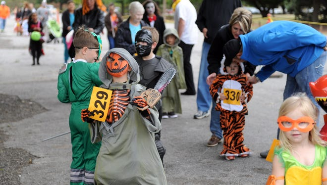 In this file photo, kids and their parents stand in line for the costume contest at Halloween in the Park at Lucy Park. The event will be 5-8 p.m. Oct. 20.