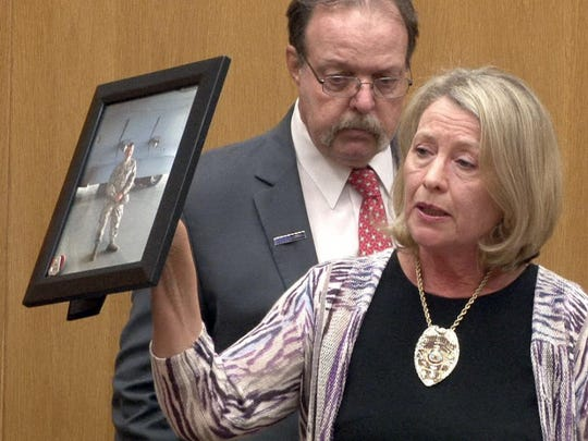 Standing with husband Richard, Deanna E. Hoffmann holds a photo of her son Christopher taken at McGuire Air Force Base on the day he died. She wore his Watchung police badge during the sentencing for Jason Wolek in State Superior Court in Toms River Friday. Wolek was sentenced to an 8-year prison term for the vehicular homicide of Hoffman, who was killed in Jackson Township while riding his motorcycle home from National Guard service.