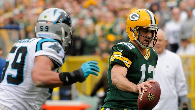 Packers quarterback Aaron Rodgers (12) runs out of bounds against the Carolina Panthers at Lambeau Field.