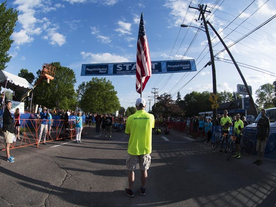 Racers and spectators listen to the National Anthem before the start of the race during the 2017 Vermont City Marathon on Sunday May 28, 2017 in Burlington. (B