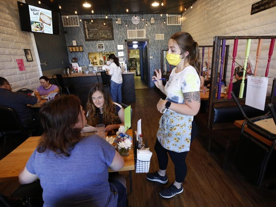 Server Jonnie Overmire goes over the menu for customers Bonnie Sitter, left, and daughter Abby, 18, at the Lambert House Cafe in Yuba City, Calif., on Monday.